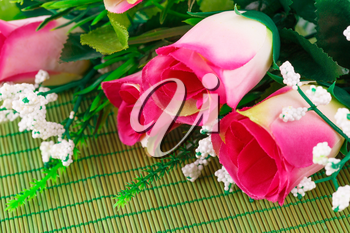 Pink fabric roses on bamboo background, closeup picture.