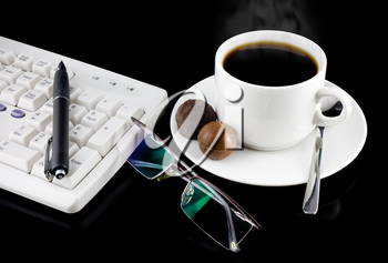 Cup of coffee, part of keyboard,mouse on a black background.