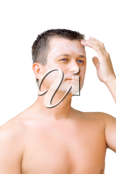 A young man puts on face cream mask . Isolated over white