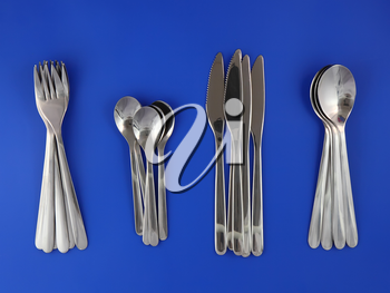 Table serving-knife,plate,fork and   on  blue background.