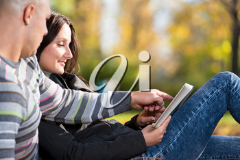 Couple Using Tablet Pc In Park