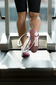 Close-Up Of Female Legs Running On Treadmill - Blurred Motion