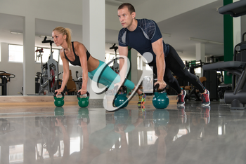 Fitness Woman And Man Working With Kettle Bell In A Gym - Kettle-bell Exercise