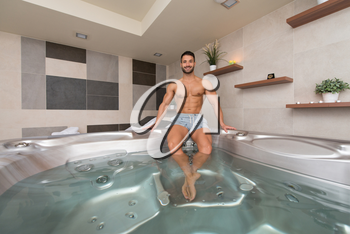 Wellness Spa - Man Relaxing in Hot Tub Whirlpool Jacuzzi Indoors at Luxury Resort Spa Retreat - Handsome Young Male Model Relaxed Resting in Water Near Pool on Travel Vacation Holiday
