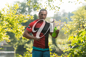 Muscular Man Resting After Exercise And Drinking From Shaker Outdoors In Nature