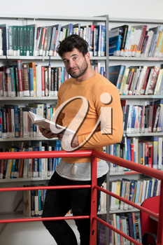 Handsome Man With Dark Hair Standing in the Library - Student Preparing Exam and Learning Lessons in School Library