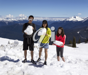 Horizontal Shot of a young man, mature mother and her daughter each holding large snowballs with Snowcap Mountains, trees and blue sky in background