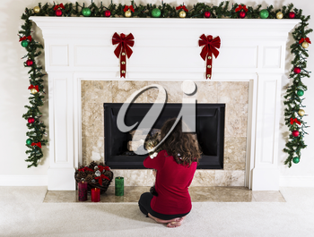 Young girl holding family cat in front of holiday decorated natural gas fire place in living room of home