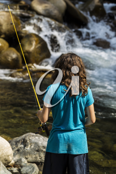 Young girl fishing in rapids of stream for trout during summer day