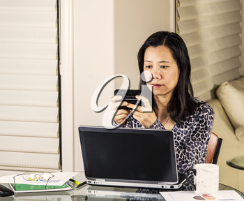 Mature women texting work message while at home office