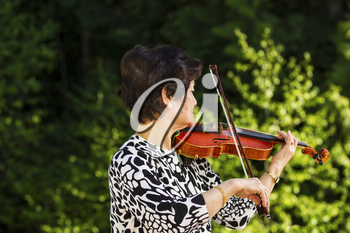 Horizontal photo of Senior Asian woman facing the forest while playing the violin outdoors with green trees in background