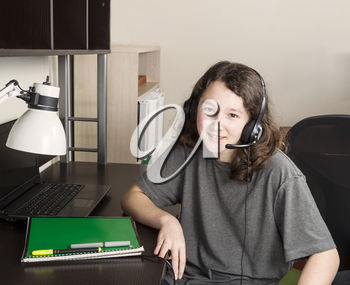Young girl getting ready to do homework with headset on while sitting at her desk