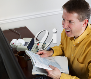 Photo of mature man, looking at data on computer monitor, working on taxes while going into a total rage of anger with office equipment in background