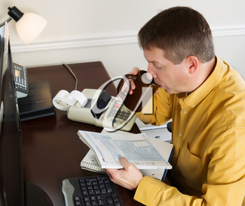 Horizontal photo of mature man looking over the tax tables while sipping on coffee in his office at home