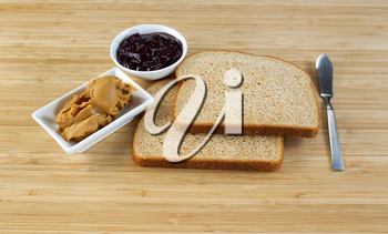 Horizontal photo of peanut butter and jelly sandwich ingredients and spread knife with natural bamboo cutting board underneath
