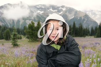 Horizontal photo of young girl, looking forward, during early spring with mountains and wild flowers in background