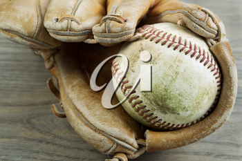 Closeup horizontal photo old dirty baseball inside of heavily used glove on rustic wood