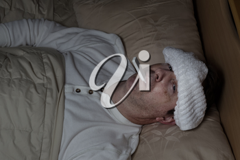 Horizontal image of mature man, with wet towel on forehead, lying down in bed testing his temperature