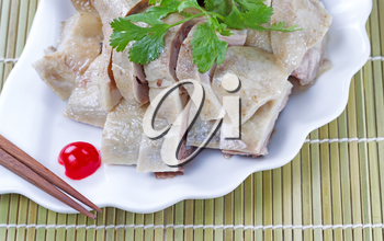 Close up image of Chinese cooked chicken, parsley, cherry and chopsticks on white plate with natural bamboo place mat background