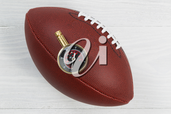 Close up of America football with air pressure gauge on top of ball with rustic white wood underneath.
