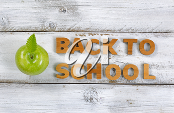 Wooden letters spelling back to school and green apple on top of rustic white boards.