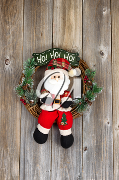 Wreath with Santa Claus symbol on rustic wood. Layout in vertical format.