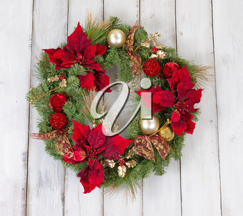 Traditional Christmas wreath on rustic white wood. Boards in vertical pattern.