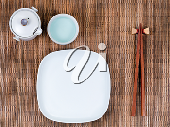 Overhead view of chopsticks, plate, cup and tea server on bamboo mat.
