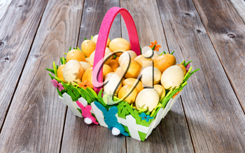 Easter Eggs in Basket on rustic wooden boards