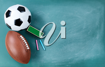 American football and soccer ball on cleaned chalkboard with eraser and chalk