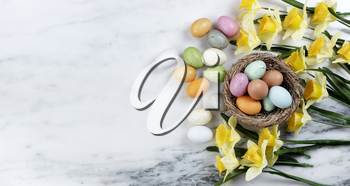 Happy Easter holiday concept with nest of colorful eggs with yellow daffodil flowers on stone background in flat lay format
