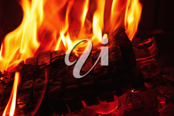 Fireplace burning. Warm burning and glowing fire in fireplace. Close up. Cozy background.
