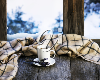White cup of coffee or tea, lavender flowers and woolen plaid located on stylized wooden window sill. Winter concept of comfort and relaxation.