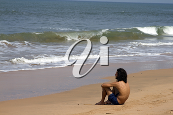 The young man with long hair sits on the coast and looks at the sea. India Goa.