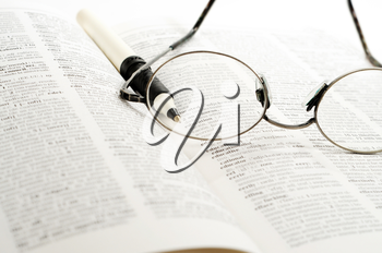 Royalty Free Photo of a Reading Glasses and a Pen on a Book