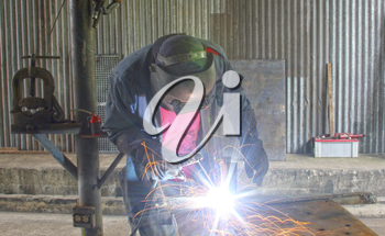 Man welding a piece of iron on a work table in a shop