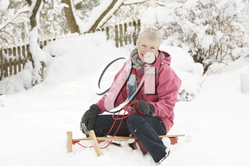 Senior Woman Sitting On Sledge In Snowy Landscape
