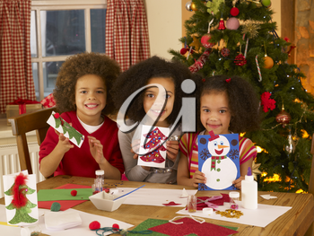 Mixed race children making Christmas cards