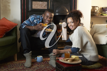 Young couple making toast on open fire