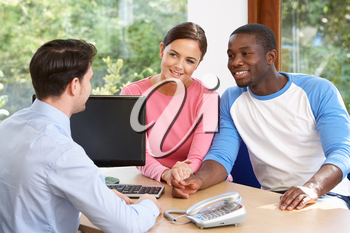 Couple Talking With Financial Advisor In Office