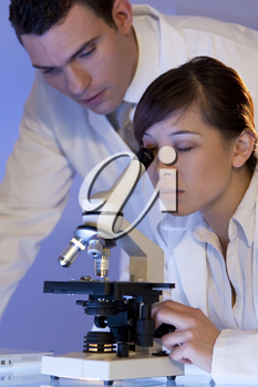 A beautiful female medical or scientific researcher using her microscope with her male colleague out of focus behind her.
