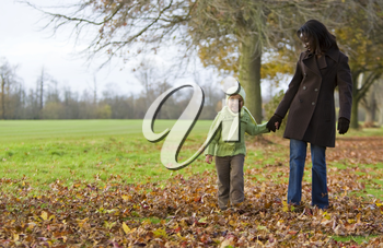 A young mixed race girl walking through the autumn leaves with her black mother