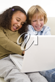 Two young children surfing the wold wide web on a laptop while sitting on a settee