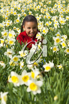 A beautiful young mixed race girl playing in a field of daffodils