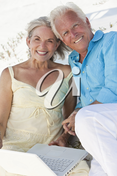 Happy senior man and woman couple together using a white laptop computer on a beach.