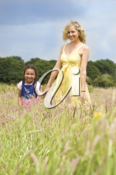 A beautiful blond haired blue eyed young woman having fun walking through a field with a mixed race young girl in a field of long grass