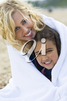 A beautiful blond haired blue eyed young woman keeping herself and her young daughter warm in a towel at the beach