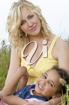 A beautiful blond haired blue eyed young woman having fun playing in a field of long grass with a mixed race young girl who is holding a yellow flower.