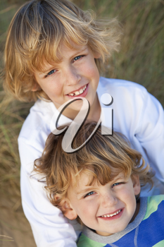 Two young boys, brithers, happy together in the grassy dunes of a sandy beach