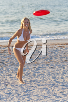 A beautiful young blond woman in a white bikini playing frisbee at the beach